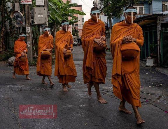 راهبان تایلندی در حال جمعآوری صدقه از ساکنان محلی +عکس